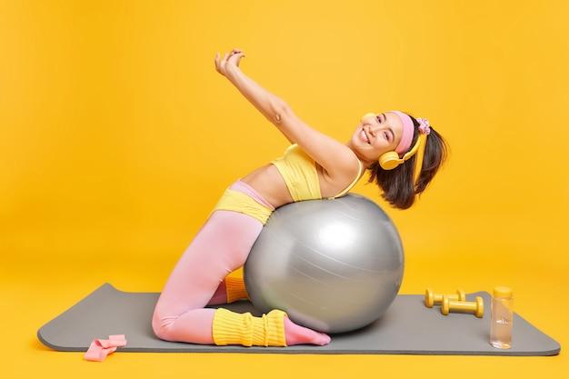 La donna si appoggia alla palla fitness allunga le braccia fa esercizi di aerobica vestita in abiti sportivi ascolta musica con le cuffie pone sul tappetino con manubri bottiglia d'acqua. fai del tuo meglio