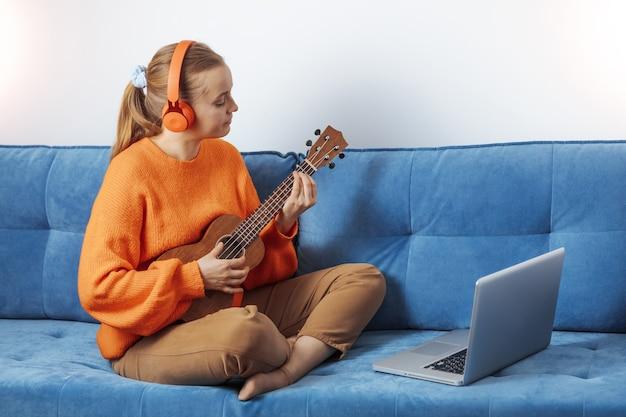 Una donna impara a suonare l'ukulele a distanza