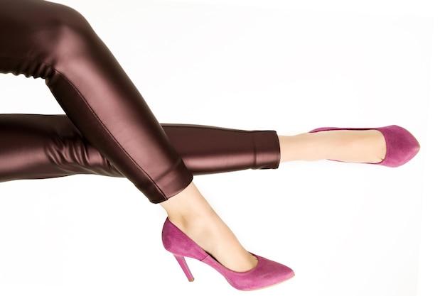 Donna in pantaloni di pelle e scarpe tacchi alti rosa su sfondo bianco. - immagine