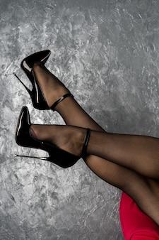 Gambe di donna in tacchi a spillo in vernice lucida nera fetish con cinturino alla caviglia vicino al muro
