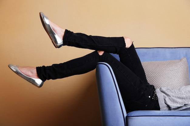 Gambe di donna sul divano con scarpe alla moda in camera