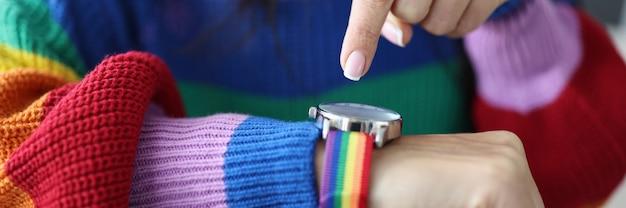 La donna con un maglione lgbt punta il dito sul quadrante dell'orologio.