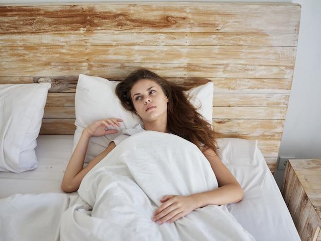 La donna si trova a letto sotto la coperta nelle emozioni di rilassamento di mattina