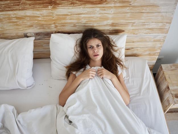 La donna giace a letto coperta di insoddisfazione per le emozioni di una coperta