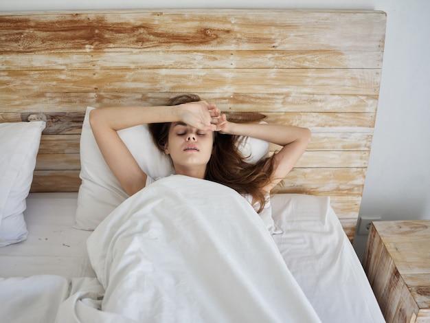 La donna giace a letto sotto le coperte con le mani sulla fronte