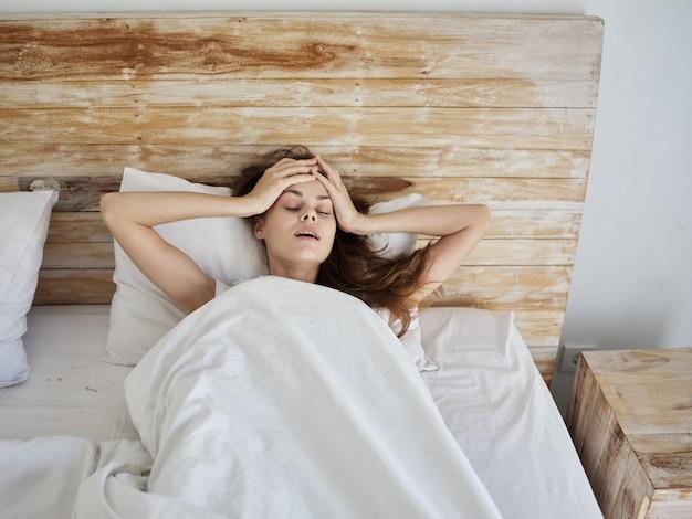 La donna giace a letto sotto le coperte e tiene le emozioni della testa. foto di alta qualità