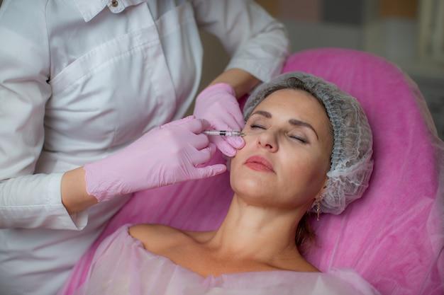 Una donna giace su un divano e subisce una puntura nella pelle del viso