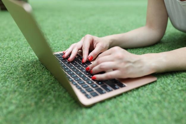 La donna si trova sul prato verde e lavora al primo piano del computer portatile