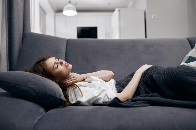 La donna si trova a casa sul divano coperto da una coperta per problemi di salute. foto di alta qualità