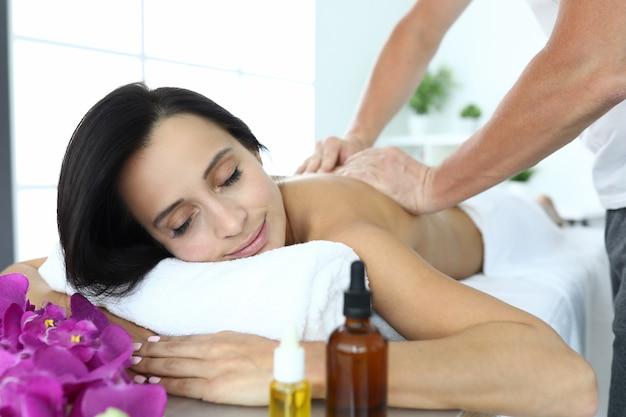 La donna si trova sul lettino da massaggio che viene massaggiata.