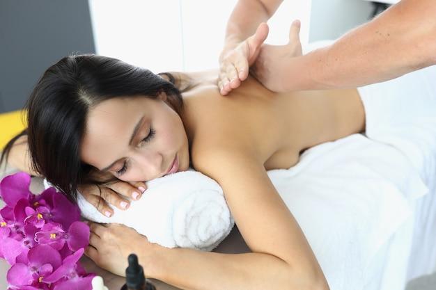 La donna si trova con gli occhi chiusi sul massaggiatore lettino da massaggio fa massaggio alla schiena. rivitalizzante e rilassante concetto di massaggio alla schiena