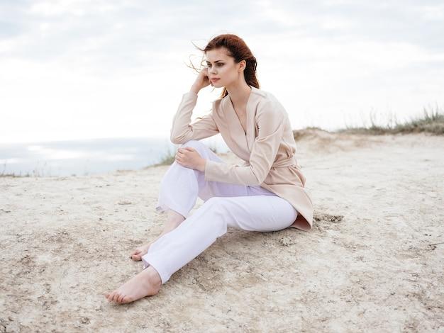 La donna in vestiti leggeri si siede sulla sabbia vicino all'oceano nella natura