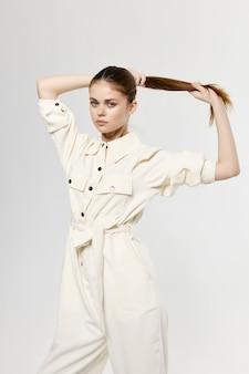 La donna in tuta leggera tocca i capelli in testa con il modello di acconciatura a coda di cavallo delle mani