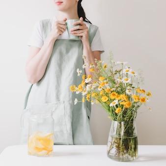 Donna in grembiule di lino che beve limonata con casa accogliente