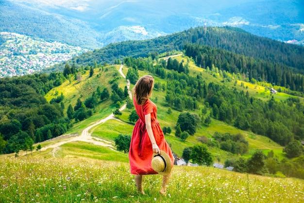 Donna in abito di lino e cappello di paglia in montagna