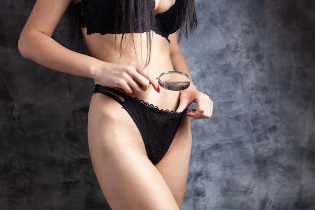 La donna in biancheria guarda sotto le mutandine con una lente d'ingrandimento