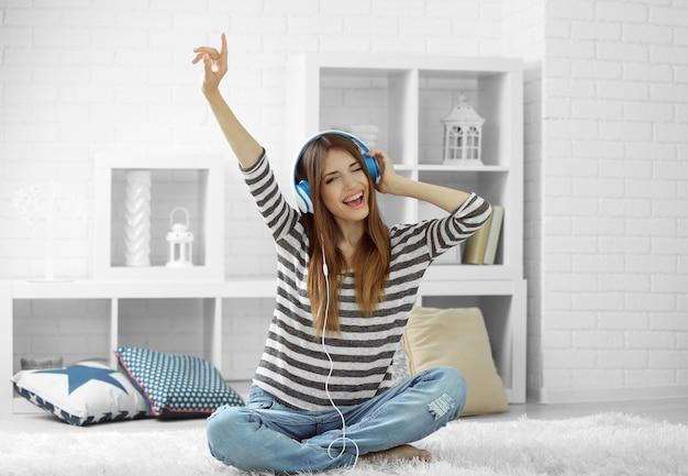 Donna che ascolta musica in cuffia sul tappeto in camera