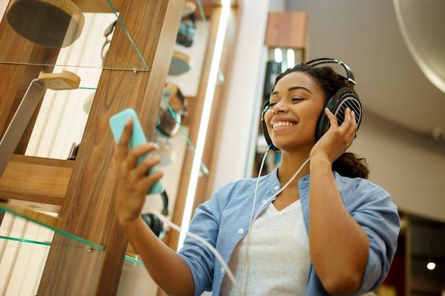 Donna che ascolta la musica nel negozio di cuffie. persona di sesso femminile nel negozio di audio, vetrina con auricolari, acquirente nel negozio multimediale