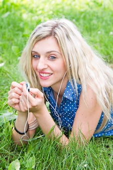 Donna che ascolta la musica sdraiata sull'erba nel parco.