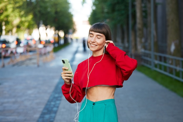 Donna che ascolta musica per strada con il telefono, donna millenaria carina in maglione rosso elegante con smartphone e auricolare e ascolta musica