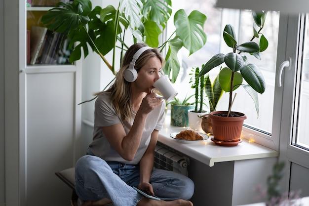 Donna che ascolta la musica indossa le cuffie wireless, seduto e guardando fuori dalla finestra, bevendo tè