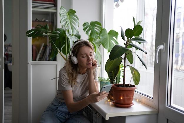 La donna che ascolta la musica indossa le cuffie bianche senza fili utilizzando lo smart phone mobile, beve il tè a casa