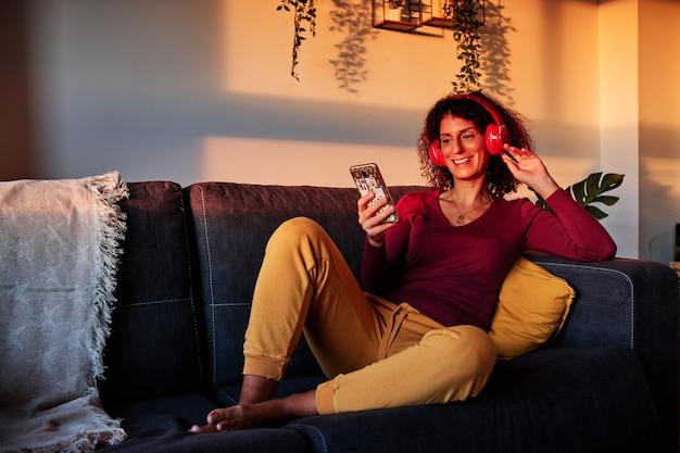 Donna che ascolta musica con le cuffie a casa durante la corantina per il coronavirus