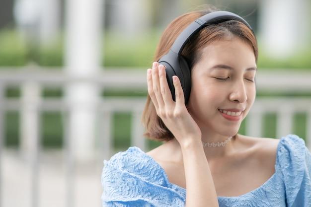 La donna ascolta la musica che indossa e tocca sopra le cuffie dell'orecchio