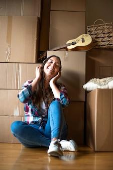 La donna ascolta la musica con le cuffie dopo il trasloco mucchio di scatole di cartone trasferimento
