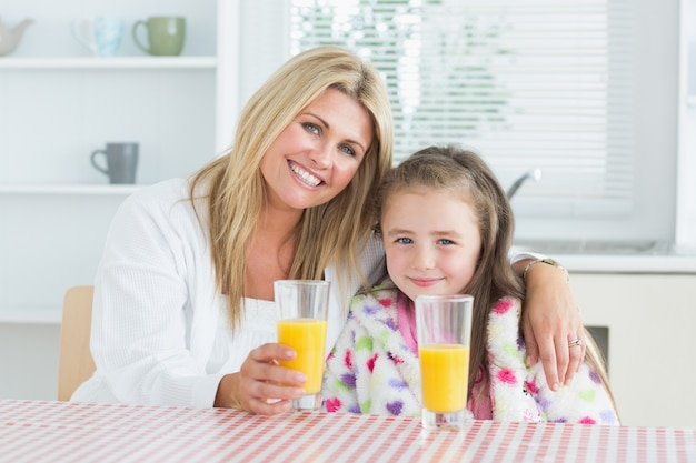 Donna e bambina che si siedono in cucina con succo
