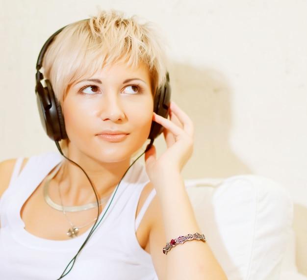 Donna in soggiorno ascoltando il lettore mp3 sorridendo