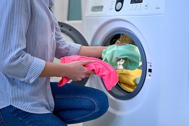 La donna carica la lavatrice con vestiti colorati al giorno del bucato