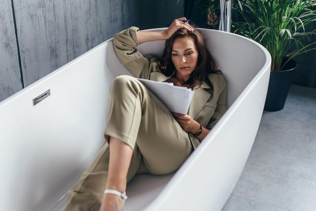 La donna si è chiusa in bagno per lavorare con i documenti. lavoro da casa.