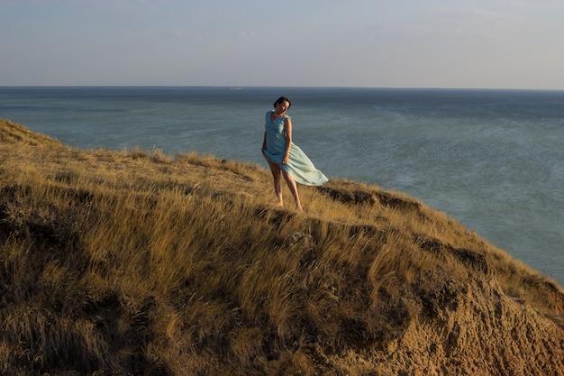 Donna in un lungo abito blu in piedi su un'alta scogliera in riva al mare o sull'oceano in una soleggiata giornata estiva ventosa.