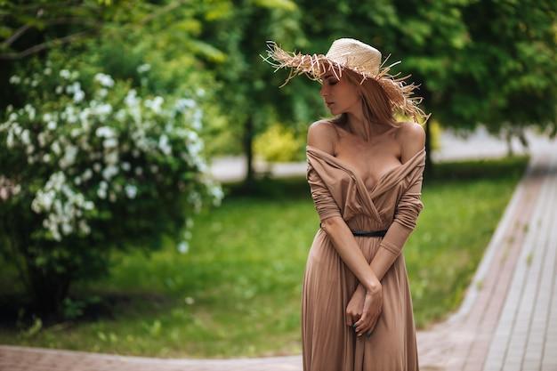Una donna con un lungo vestito marrone e un cappello di paglia cammina in un parco estivo
