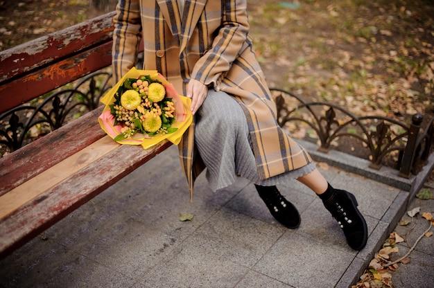 Donna in abito lungo e cappotto plaid seduto sulla panchina con un mazzo di fiori gialli