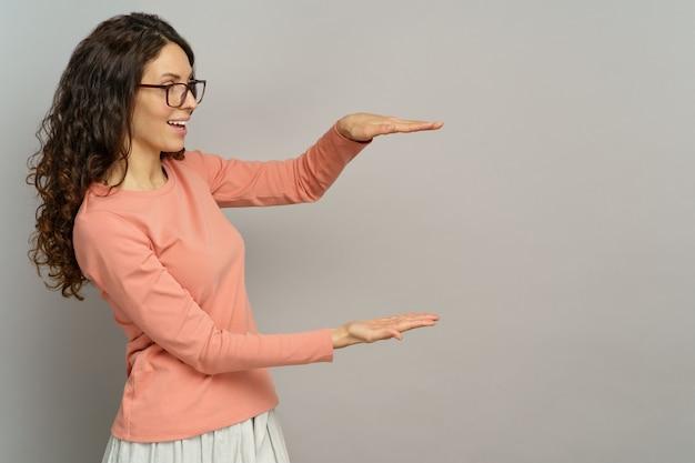 La donna guarda qualcosa in mano tiene il palmo aperto per la presentazione su copyspace su sfondo grigio