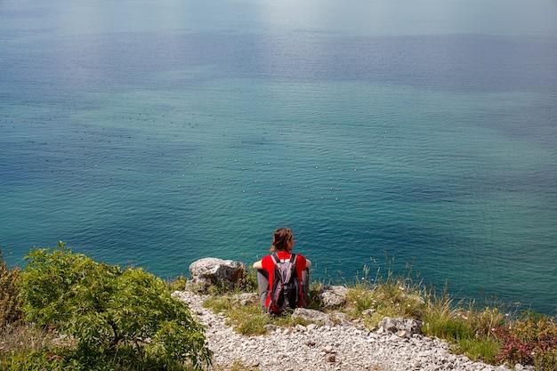 Una donna che guarda il mare adriatico dal bordo carsico vicino a trieste, italia