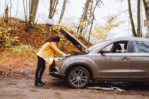 La donna alla ricerca di un'auto rotta sulla strada di campagna ha foresta intorno