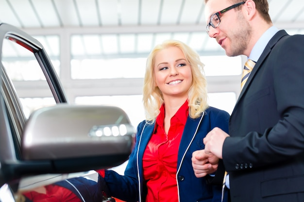 Donna che esamina automobile nel concessionario auto