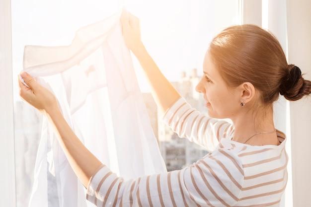 Donna che guarda i vestiti puliti