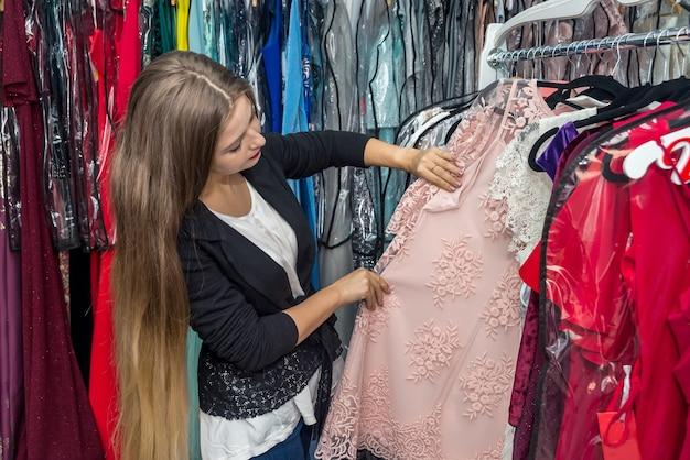 Donna in cerca di un vestito nel negozio di abbigliamento