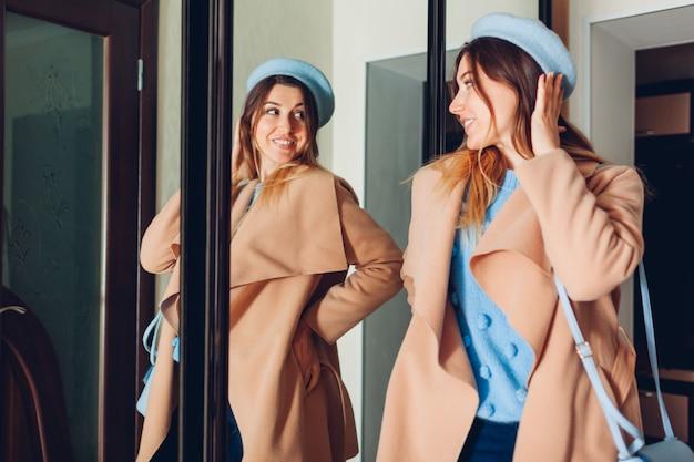 Donna che esamina la sua riflessione in specchio. la ragazza alla moda che prova la molla copre sopra dal guardaroba a casa