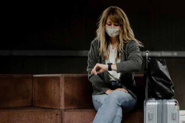 Donna che guarda l'orologio mentre aspetta il treno durante la pandemia di coronavirus