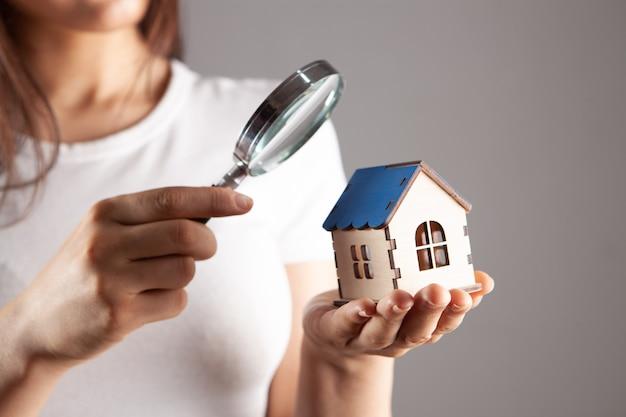 Donna che guarda la casa attraverso una lente d'ingrandimento
