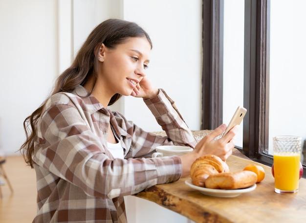 Donna alla ricerca di informazioni su internet, sorridente e utilizzando il cellulare, gustando la colazione. concetto per la dipendenza digitale, routine mattutina. domenica vita lenta