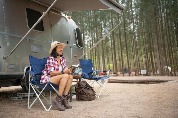 Donna che guarda il laptop vicino al campeggio. vacanza in roulotte. viaggio di vacanza in famiglia, viaggio di vacanza in camper. donna che legge un libro all'interno del bagagliaio dell'auto. apprendimento femminile in pausa viaggio, posa