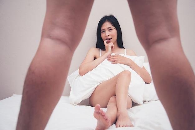 La donna nell'attesa equipaggia il pene nella camera da letto