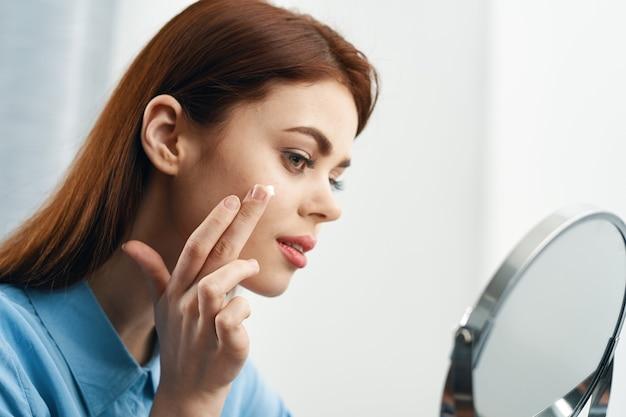 Donna che si guarda allo specchio cosmetici cura personale