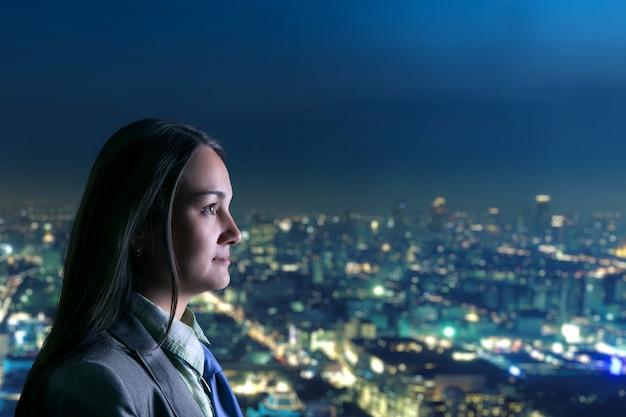 Donna che guarda la città di notte